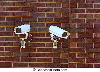 Two Security Cameras on Brick Wall