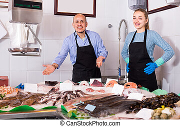 Two sellers in fish store . - Ordinary fish and seafood ...