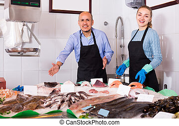 Two sellers in fish store . - Two cheerful sellers standing ...