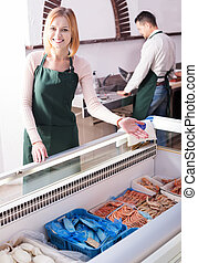 Two sellers of frozen fish - Portrait of two positive shop ...