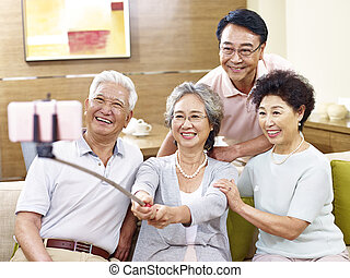 two senior asian couples taking a selfie