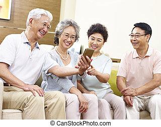 two senior asian couples taking a selfie