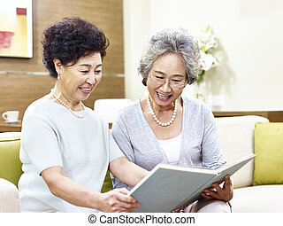 two senior asian women reading a book together