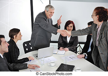 Two senior business people shaking hands at meeting