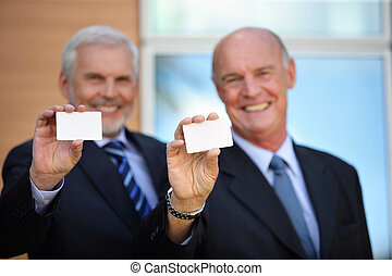 Two senior businessman holding cards