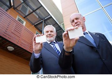 Two senior businessmen displaying their calling-cards