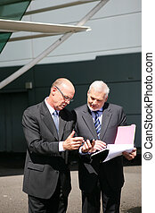 Two senior businessmen going over paperwork outdoors