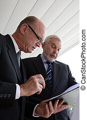 Two senior businessmen looking over a document
