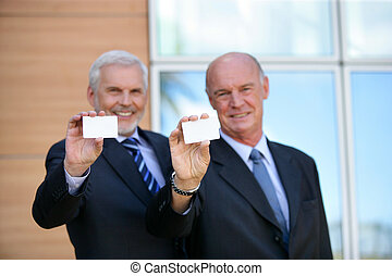 Two senior businessmen showing cards