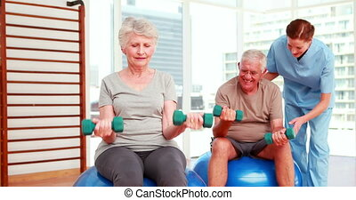 Two senior citizens exercising with physiotherapist at the...