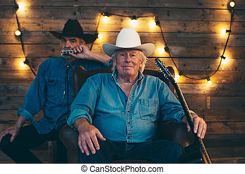 Two senior country and western musicians sitting on chair in...