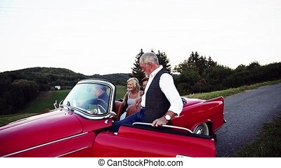 Two senior couples getting in cabriolet on a road trip in...