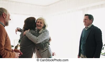 Two senior couples greeting one another at a party at home....