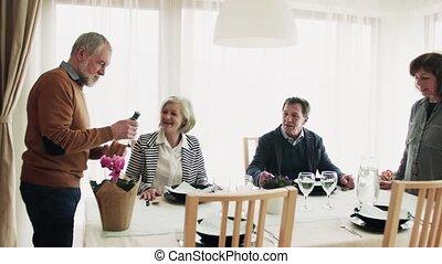 Two senior couples having dinner at home.