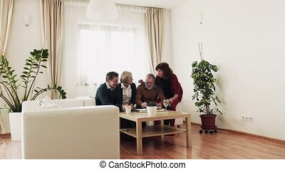 Two senior couples looking at photographs at home. - Two...