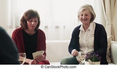 Two senior couples playaing cards at home.