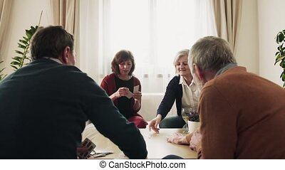 Two senior couples playing cards at home.