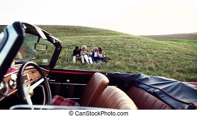 Two senior couples sitting by cabriolet on a road trip in...