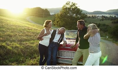 Two senior couples standing by cabriolet on a road trip in...