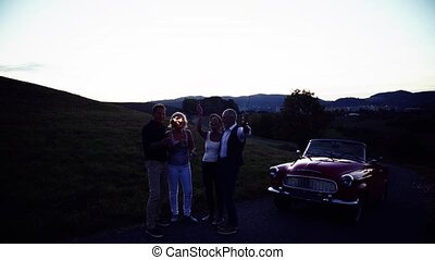 Two senior couples with sparklers on a road trip in summer,...