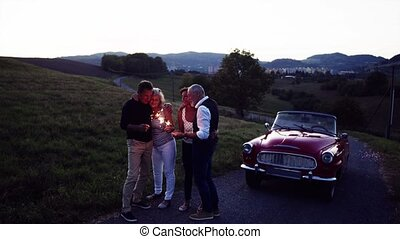 Two senior couples with sparklers standing by cabriolet on a...