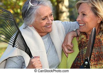 two senior friends gardening