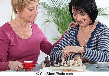 two senior girlfriends playing chess