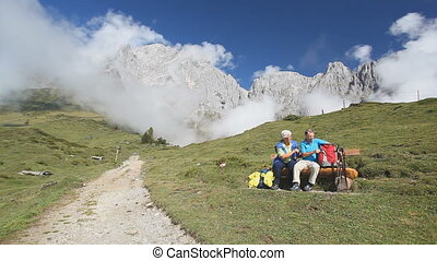two senior hikers on bench near path