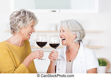 Two senior ladies celebrating with red wine standing...