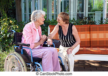 Two senior ladies chatting on a garden bench