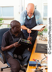 two senior men assembly electronic equipment in workshop
