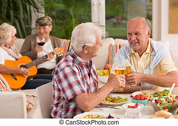 Two senior men drinking beer and their wives playing guitar...