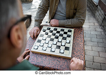 Two senior men playing checkers outdoor