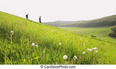 Two senior men running outside on green hills.