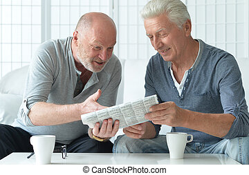 two senior men with newspaper and tea at home