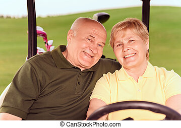 Two senior people driving in cart