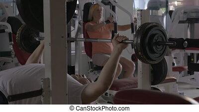 Two senior people training on fitness machines