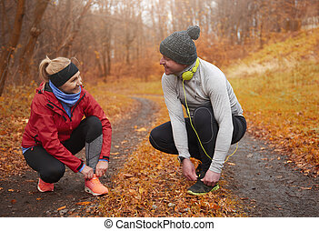 Two senior runners tying their shoelace