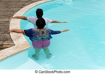 Two senior women doing aqua gym exercise in outdoor swimming pool.