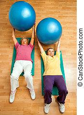 Two senior women doing gym ball exercises on floor.