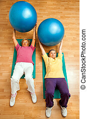 Two senior women doing gym ball exercises on floor.