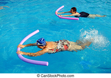 Two senior women doing swimming exercise in pool.