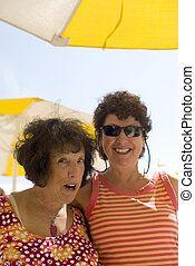 two senior women friends happy at beach