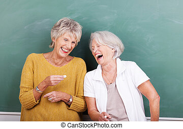 Two senior women sharing a good joke standing together in...