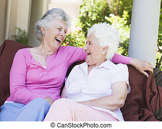 Two senior women sitting outdoors on a chair