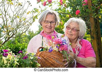 Two senior women standing with basket in garden