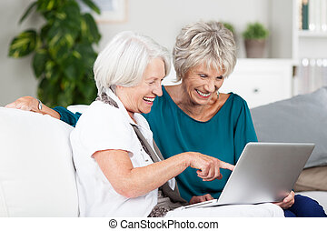 Two senior women surfing the internet laughing and...