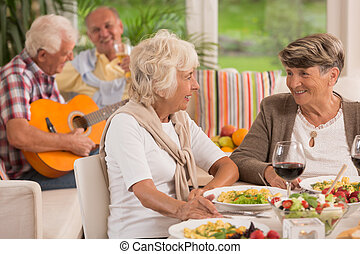 Two senior women talking and drinking wine, in the...