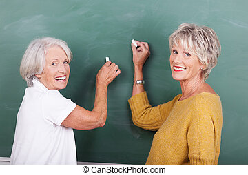 Two senior women writing on a blackboard