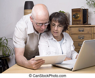 two seniors play with a tablet computer